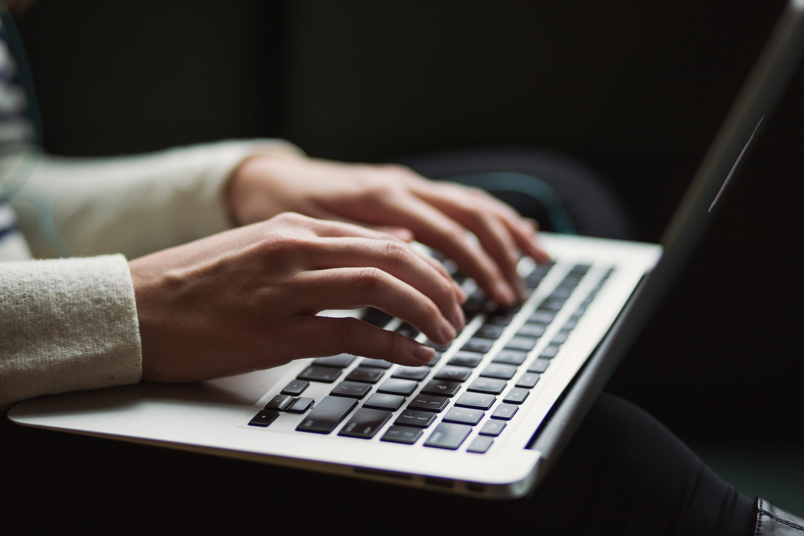 A person typing on a Macbook laptop